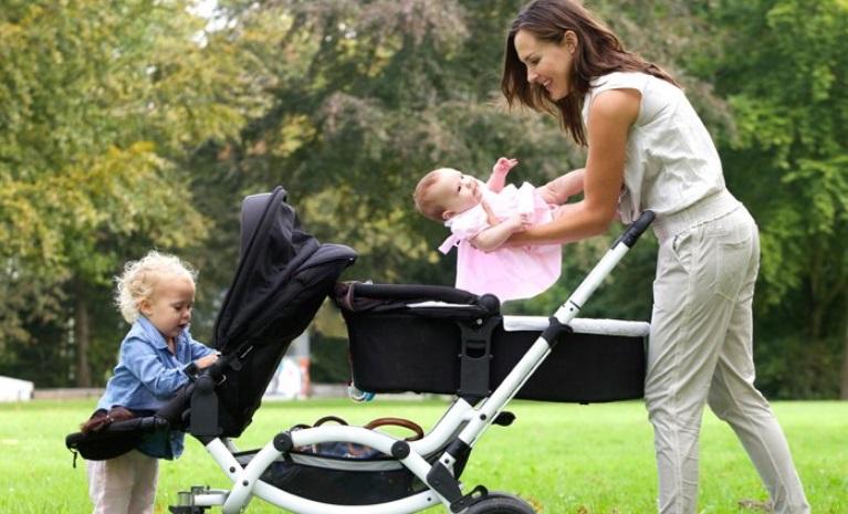 Maman avec deux enfants et une poussette double