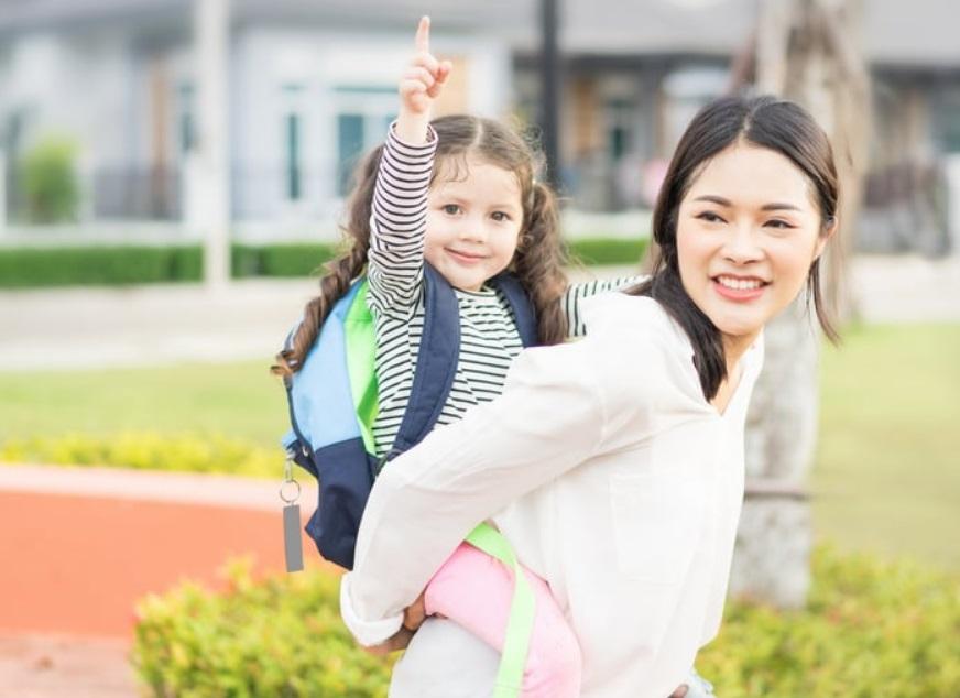 Une maman et sa fille sur le dos