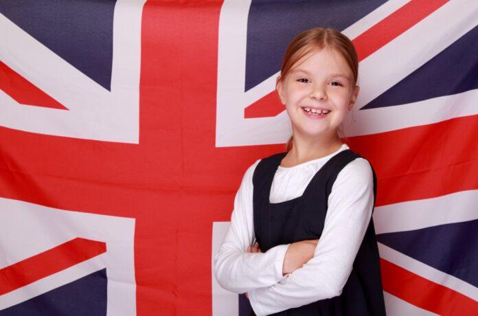 petite fille en robe t-shirt blanc devant drapeau britannique