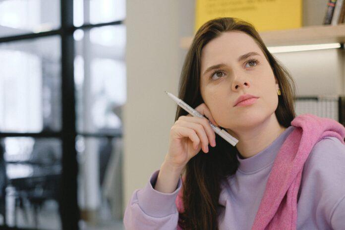 adolescente pull violet stylo en main en classe séjour linguistique